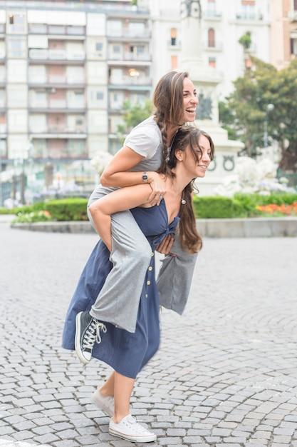 Glimlachende jonge vrouw die haar meisjestribbing op rit neemt op straat Gratis Foto