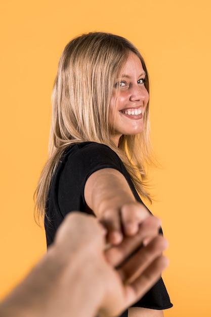 Glimlachende jonge vrouw die haar vriend trekt tegen gele muur Gratis Foto