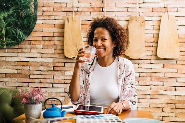 Glimlachende jonge vrouw die het glas sap drinkt Gratis Foto
