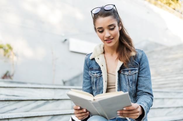 Glimlachende jonge vrouw die jasje zittend op een bankje buiten draagt, het lezen van boek Premium Foto