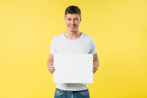 Glimlachende jonge vrouw die leeg aanplakbiljet toont tegen gele achtergrond Gratis Foto
