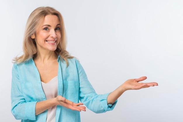 Glimlachende jonge vrouw die tegen witte achtergrond voorstellen Gratis Foto