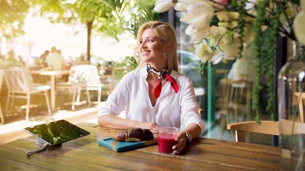 Glimlachende jonge vrouw die van de drank en het brood in het restaurant geniet Gratis Foto