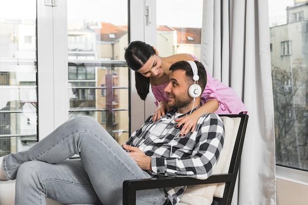 Glimlachende jonge vrouw die zich achter de man zit op stoel luisteren muziek op de koptelefoon Gratis Foto
