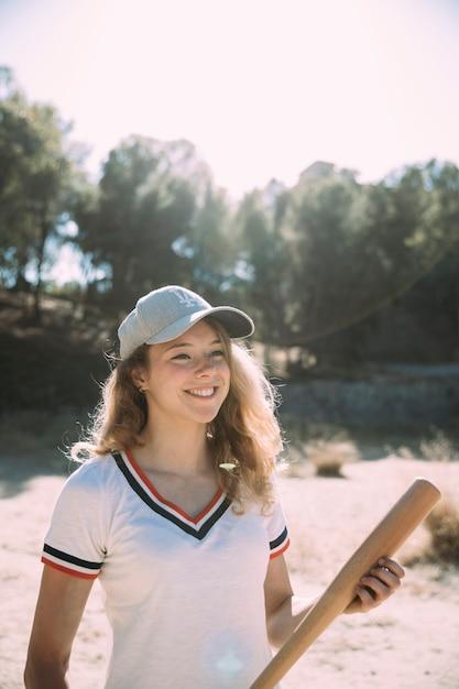 Glimlachende jonge vrouw die zich met honkbalknuppel bevindt Gratis Foto
