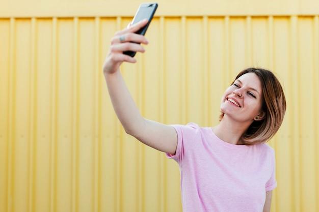 Glimlachende jonge vrouw die zich tegen golf geel metaalblad bevinden die selfie op mobiele telefoon nemen Gratis Foto