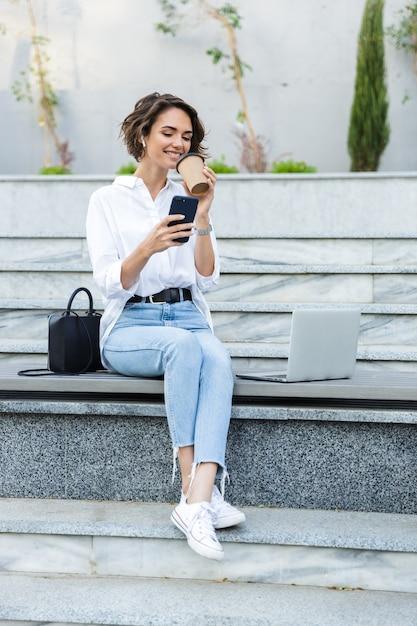 Glimlachende jonge vrouw in oortelefoons die buiten zitten Premium Foto