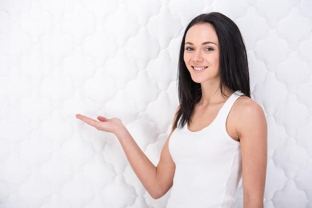Glimlachende jonge vrouw met orthopedische matras. Premium Foto