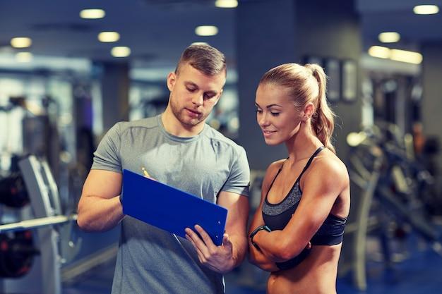 Glimlachende jonge vrouw met persoonlijke trainer in gymnastiek Premium Foto