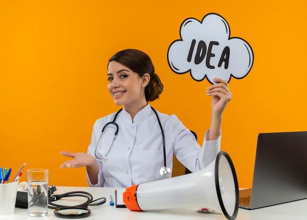 Glimlachende jonge vrouwelijke arts die medische mantel draagt met een stethoscoop zit aan bureau werk op computer met medische hulpmiddelen idee zeepbel houden op isolatie gele achtergrond Gratis Foto