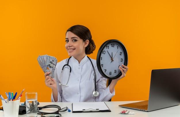 Glimlachende jonge vrouwelijke arts die medische mantel draagt met een stethoscoop zittend aan een bureau werkt op de computer met medische hulpmiddelen die muurklok en contant geld op isolatie gele achtergrond houdt Gratis Foto