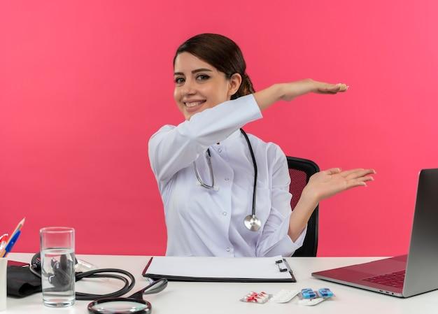 Glimlachende jonge vrouwelijke arts die medische mantel met een stethoscoop zit aan het bureau werkt op computer met medische hulpmiddelen die grootte met exemplaarruimte tonen Gratis Foto