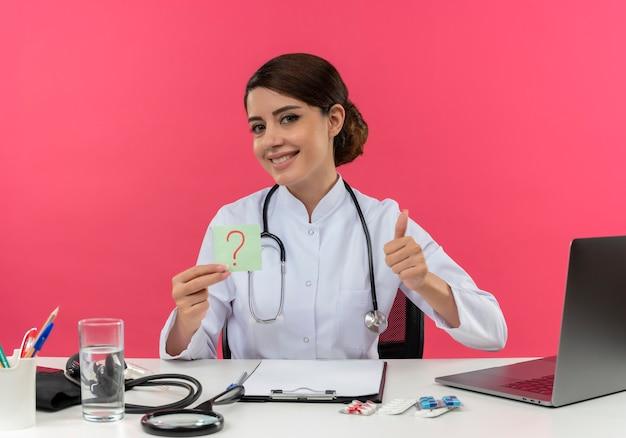 Glimlachende jonge vrouwelijke arts die medische mantel met stethoscoop draagt die aan bureau zit werkt op computer met medische hulpmiddelen die vraagteken houdt markeert haar duim omhoog op roze muur Gratis Foto