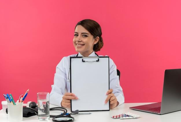 Glimlachende jonge vrouwelijke arts die medische mantel met stethoscoop zittend aan bureau werkt op computer met medische hulpmiddelen die klembord met exemplaarruimte houden Gratis Foto