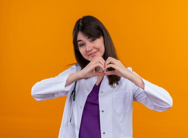 Glimlachende jonge vrouwelijke arts in medisch kleed met het hart van stethoscoopgebaren met beide handen op geïsoleerde oranje achtergrond met exemplaarruimte Gratis Foto