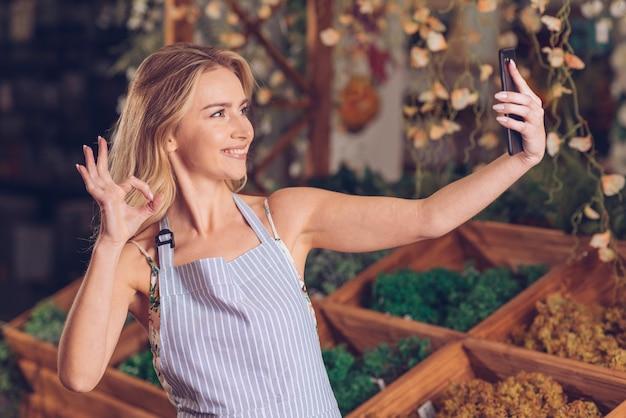 Glimlachende jonge vrouwelijke bloemist die selfie op slimme telefoon nemen die ok gebaar in de winkel tonen Gratis Foto