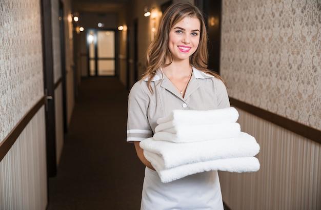 Glimlachende jonge vrouwelijke huishoudster die gevouwen handdoeken in hotelgang dragen Gratis Foto