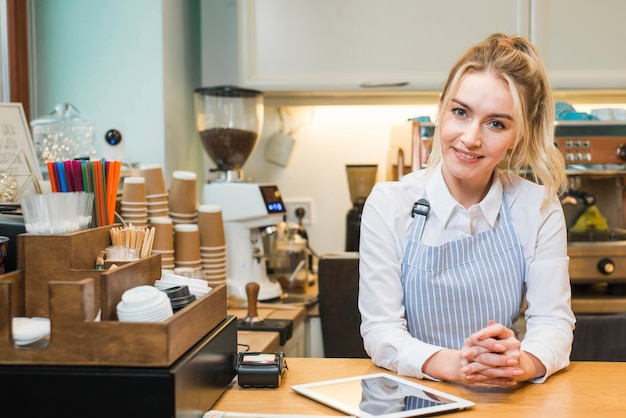 Glimlachende jonge vrouwelijke ondernemer die zich in de koffiewinkel bevindt met digitale tablet Gratis Foto