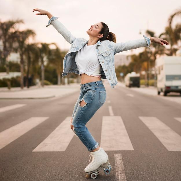Glimlachende jonge vrouwelijke skater die op het zebrapad in evenwicht brengt Gratis Foto