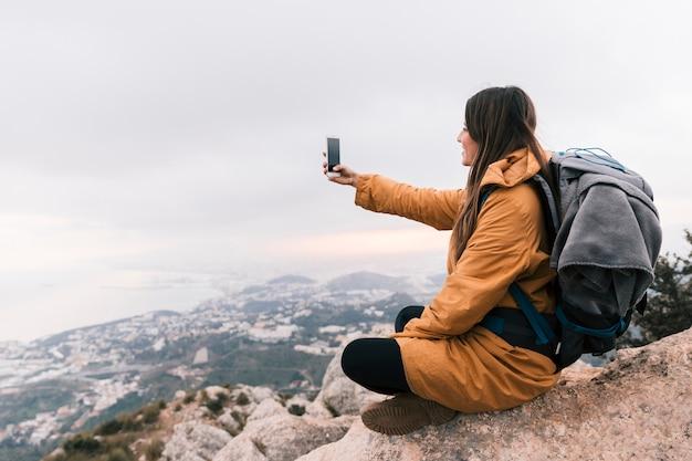 Glimlachende jonge vrouwelijke wandelaarzitting bovenop berg die selfie op mobiele telefoon nemen Gratis Foto