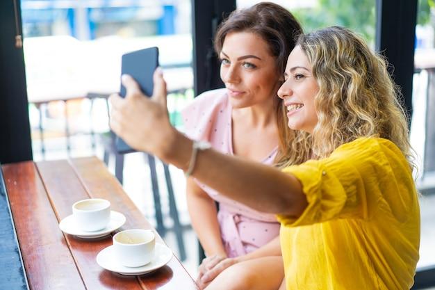 Glimlachende jonge vrouwen die selfie foto en het drinken koffie nemen Gratis Foto