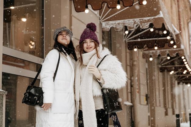 Glimlachende jonge vrouwen die warme de winterkleding dragen chatten Premium Foto