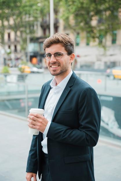 Glimlachende jonge zakenman die meeneemkoffiekop ter beschikking houden Gratis Foto
