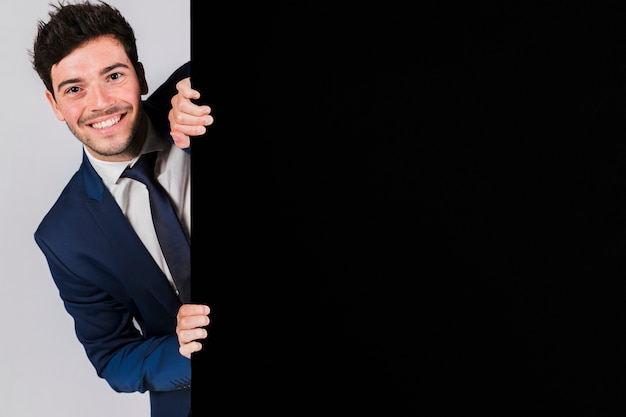 Glimlachende jonge zakenman die van het zwarte aanplakbiljet gluren Gratis Foto