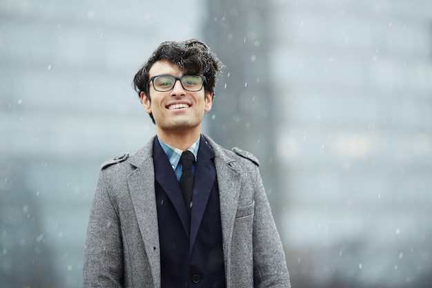 Glimlachende jonge zakenman in sneeuw Gratis Foto