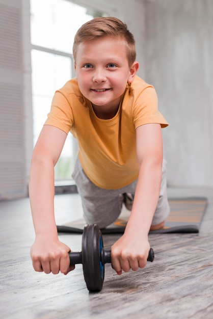 Glimlachende jongen die ab de oefening van de wieluitrol op hardhoutvloer doen Gratis Foto