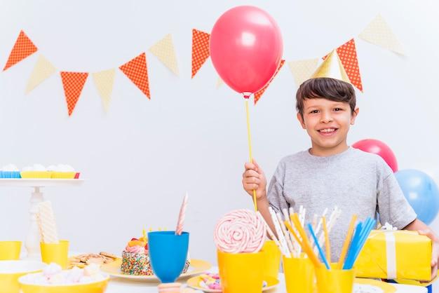 Glimlachende jongen die de holdingsballon en gift dragen die van de partijhoed zich achter verscheidenheid van voedsel op lijst bevinden Gratis Foto