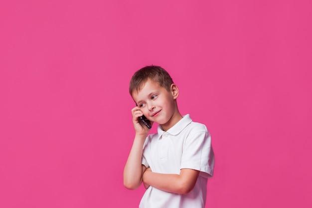 Glimlachende jongen die op cellphone over roze muurachtergrond spreekt Gratis Foto