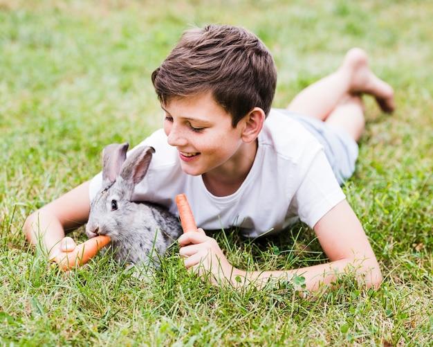 Glimlachende jongen die op groene gras voedende wortel aan konijn liggen Gratis Foto