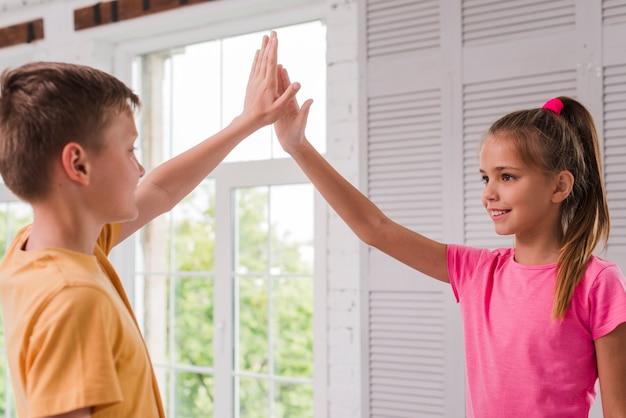 Glimlachende jongen en meisje die hoogte vijf geven dichtbij het venster Gratis Foto