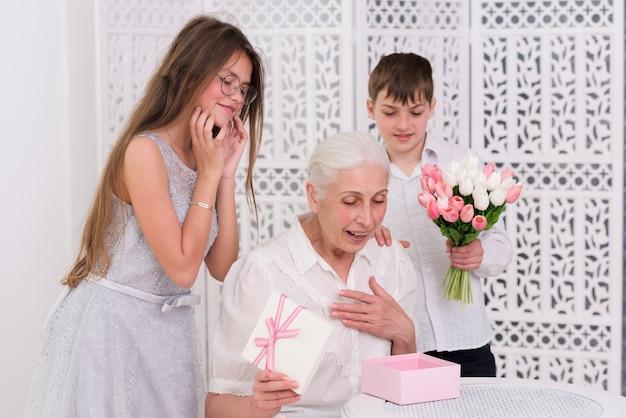 Glimlachende jongen en meisje die zich achter verraste grootmoeder bevinden Gratis Foto
