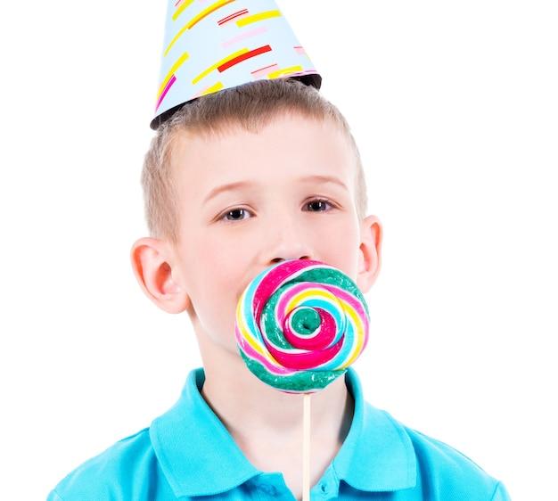 Glimlachende jongen in blauw t-shirt en feestmuts met gekleurd suikergoed - dat op wit wordt geïsoleerd. Gratis Foto