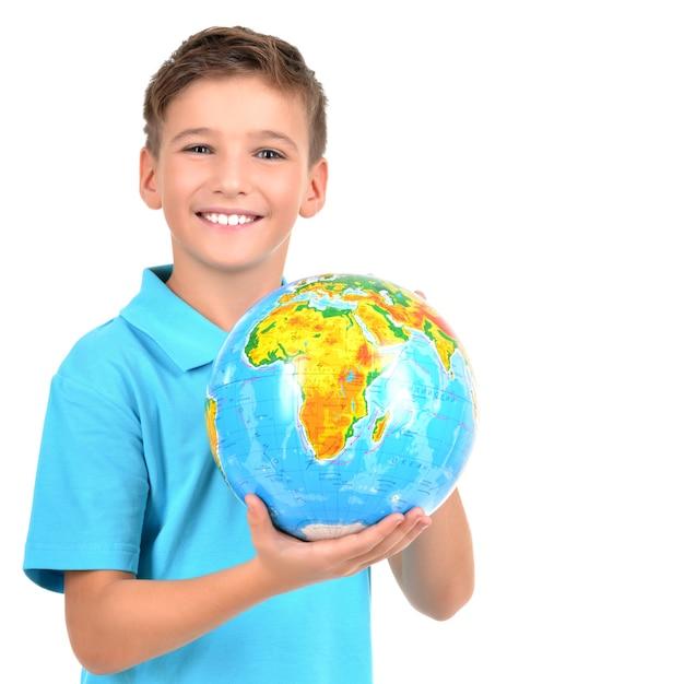 Glimlachende jongen in toevallige holdingsbol in handen die op wit worden geïsoleerd Gratis Foto