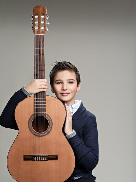 Glimlachende jongen met gitaar. Gratis Foto