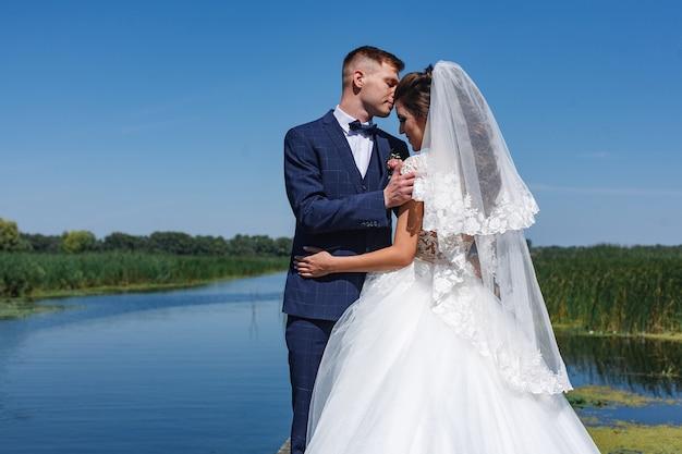 Glimlachende jonggehuwden kijken elkaar voorzichtig aan en knuffelen. portret een huwelijkspaar die dichtbij rivier stellen. Premium Foto
