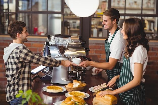 Glimlachende kelners die een cliënt dienen Premium Foto