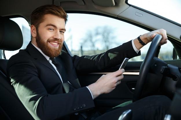 Glimlachende knappe bedrijfsvrouw die telefoon met behulp van terwijl het zitten in auto Premium Foto