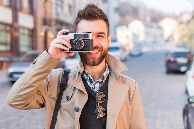 Glimlachende knappe jonge mens op stadsstraat die een beeld van uitstekende camera nemen Gratis Foto