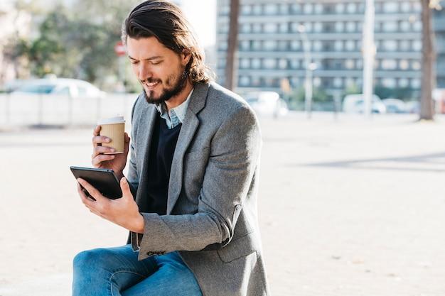 Glimlachende knappe mens die mobiele telefoon bekijken die beschikbare koffiekop houden Gratis Foto
