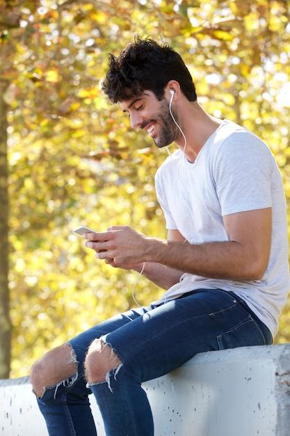 Glimlachende knappe mensenzitting buiten met hoofdtelefoons en mobiele telefoon Premium Foto