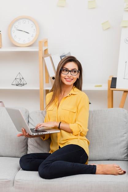 Glimlachende laptop houden en vrouw die weg kijken Gratis Foto