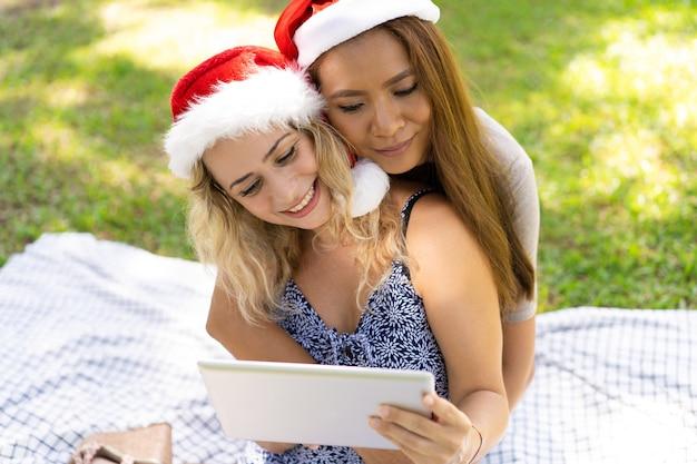 Glimlachende lesbische meisjes die terwijl het letten van video op tablet omhelzen Gratis Foto