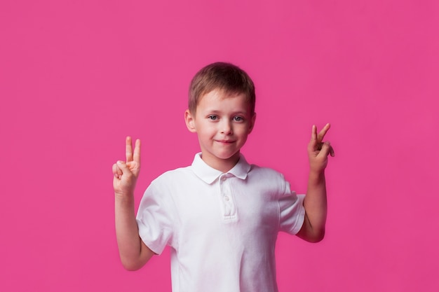 Glimlachende leuke kleine jongen die overwinningsteken op roze achtergrond toont Gratis Foto