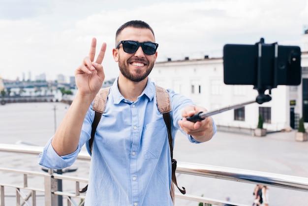 Glimlachende man die selfie met overwinningsgebaar nemen op mobiele telefoon Gratis Foto