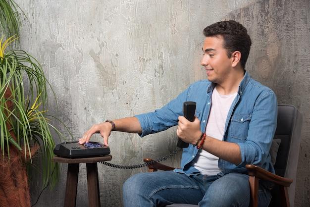 Glimlachende man een nummer typen op de telefoon en zittend op een stoel. hoge kwaliteit foto Gratis Foto