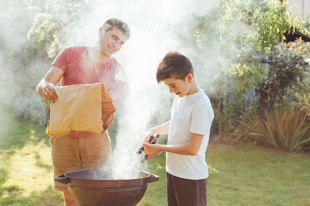Glimlachende man en jongen die steenkool in barbecue zetten bij park Gratis Foto